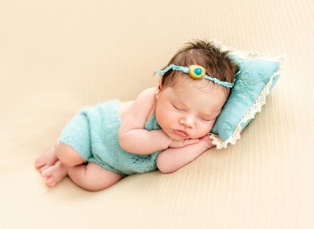 Newborn baby sleeping on a little pillow