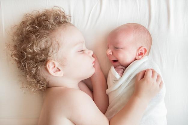 兄の小さな男の子の隣で寝ている新生児