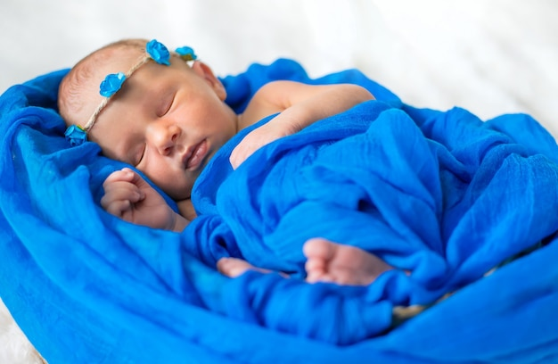 青い背景で眠っている新生児。セレクティブフォーカス。人。