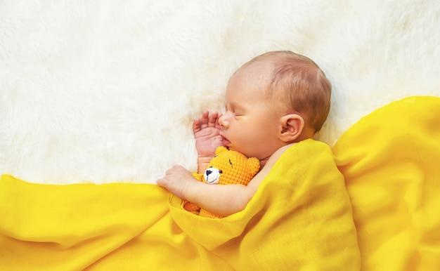 Новорожденный ребенок спит на белом фоне. выборочный фокус. люди.