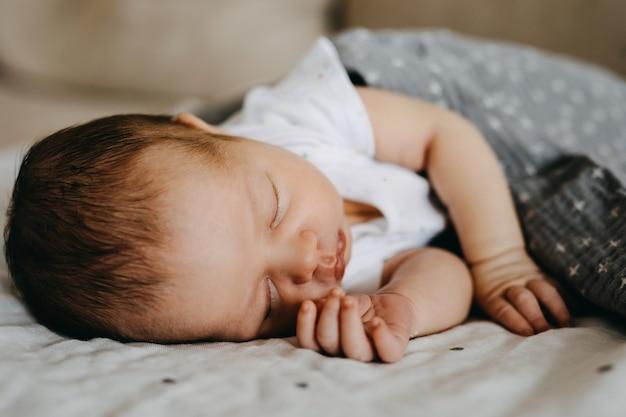 彼女の側で寝ている生まれたばかりの赤ちゃん