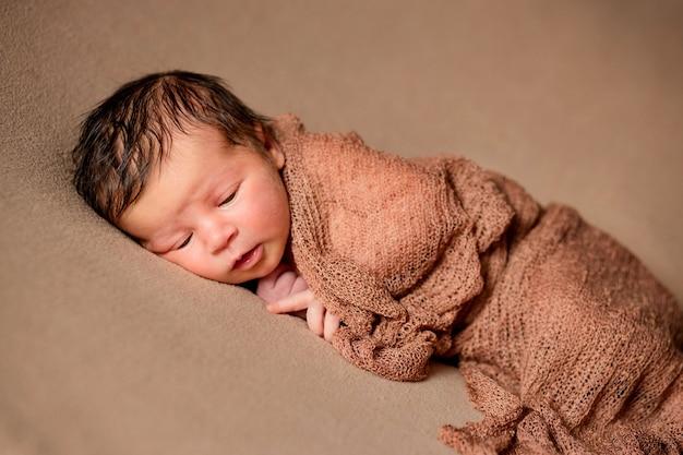 Новорожденный ребенок мирно спит с клетчатой тканью на коричневом фоне.