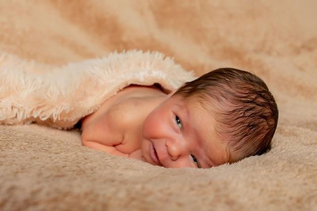 Новорожденный ребенок спит, опираясь на свои руки и локти, на коричневой поверхности.