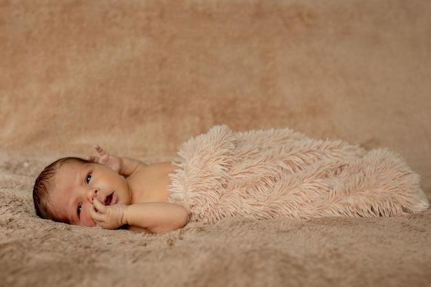 Новорожденный ребенок спит, опираясь на свои руки и локти на коричневом