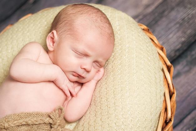頬の下で手を寝ている生まれたばかりの赤ちゃん