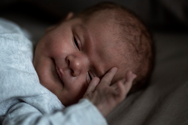 A newborn baby sleeps 1 week. close-up. low key. love and tenderness.