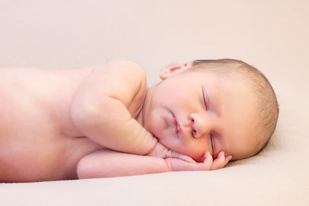 生まれたばかりの赤ちゃんは眠って微笑む。美しい眠っている赤ちゃんの肖像画を閉じる