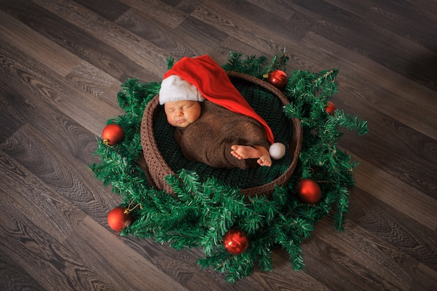 Newborn baby sleeps in a red cap with a pompom in a christmas wreath