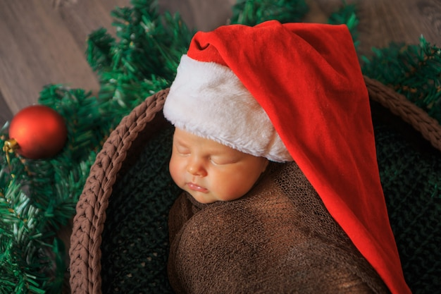 A newborn baby sleeps in a red cap with a pompom in a christmas wreath