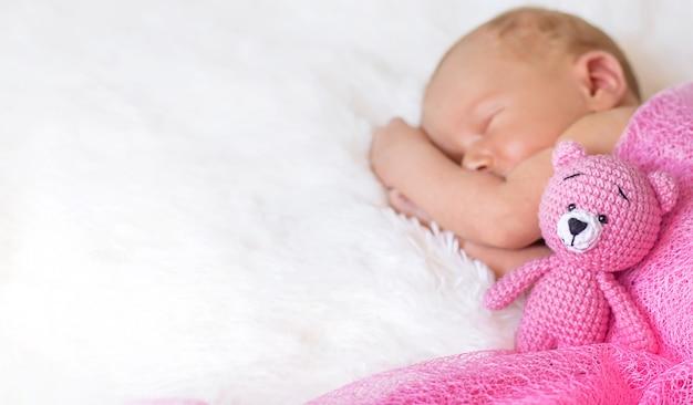 A newborn baby sleeps with a teddy bear. selective focus. people.