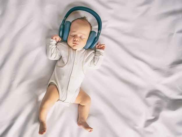 Newborn baby smiling listening to music with headphones and lying on white sheet in the crib, happy carefree childhood of the baby, toned image, top view