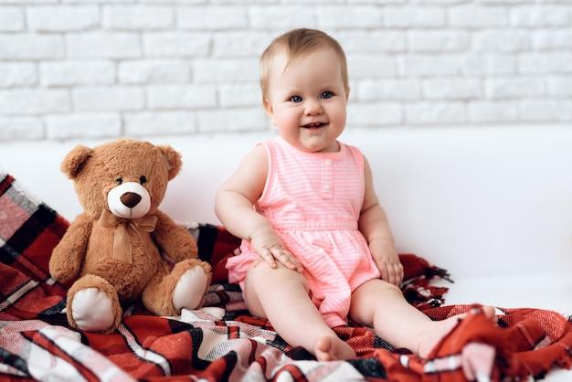 Newborn baby on sofa with plush bear.