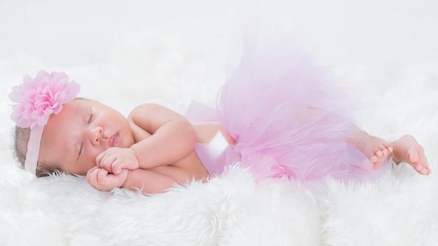 ピンクの花の冠をかぶった新生児
