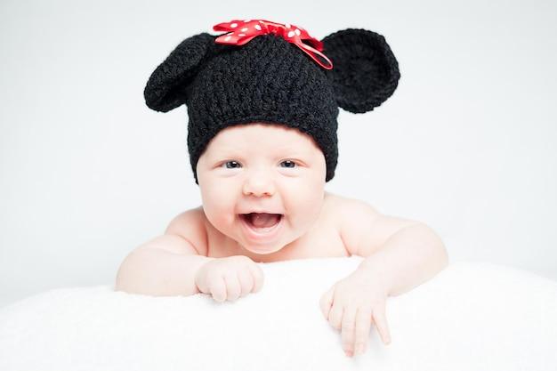 Новорожденный ребенок в шляпе на голове, лежа на одеяле улыбается милая новорожденная девочка