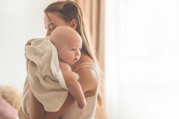Новорожденный ребенок с матерью на кровати