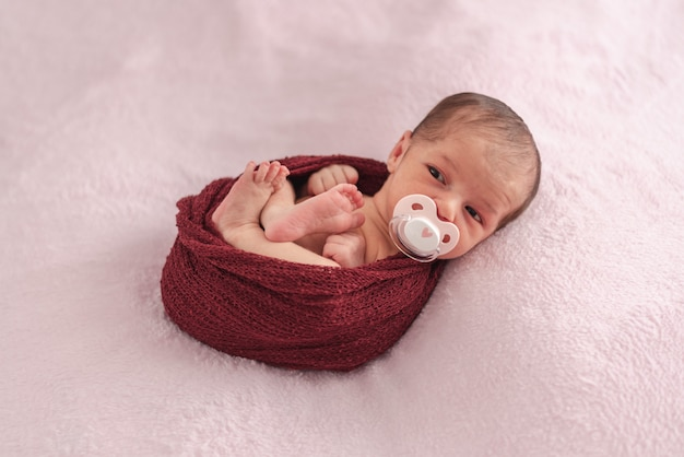 Newborn baby with pacifier tucked in a ball of wool