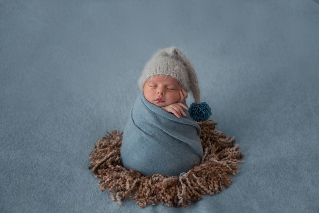Newborn baby with white beret and wrapped with blue shawl.