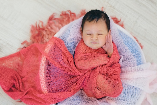 Newborn baby wrapped in a blanket sleeping in a basket. concept of childhood, healthcare, ivf