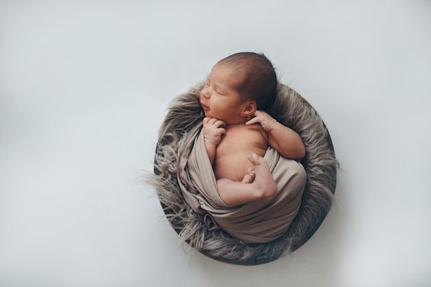 Newborn baby wrapped in a blanket sleeping in a basket. concept of childhood, healthcare, ivf.