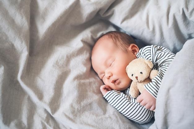 천 배경의 유아용 침대에 귀여운 부드러운 장난감을 가지고 평화롭게 자고 있는 1주일 된 신생아 소년