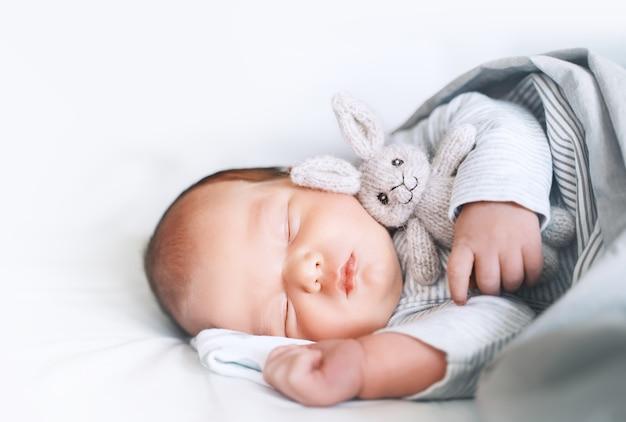 Newborn child boy one week old sleeping peacefully with a cute soft toy in crib in cloth background