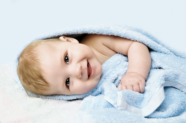 Newborn child relaxing in bed after bath or shower.