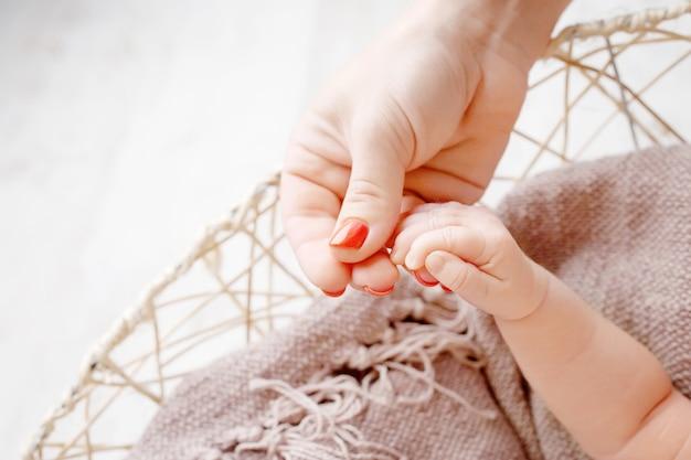 母の手で生まれたばかりの子供の手。ママと彼女の子供。幸せな家族の概念。マタニティの美しい概念図