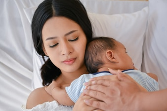 Newborn Concept. Mother and child on a white bed.