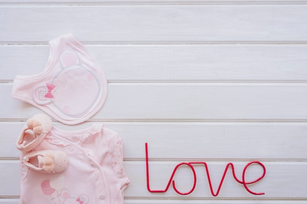 Newborn concept with baby clothes and love letters