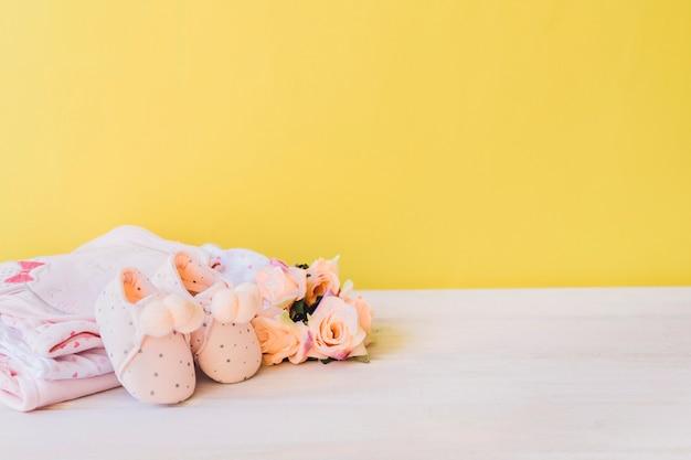 Концепция новорожденного с одеждой и розой