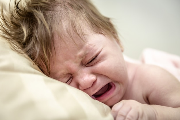 Newborn crying baby girl. new born child tired and hungry in bed. children cry. bedding for kids. infant screaming.