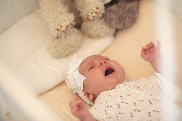 生まれたばかりのかわいい女の赤ちゃんがベビーベッドに横たわって、母親を見ています