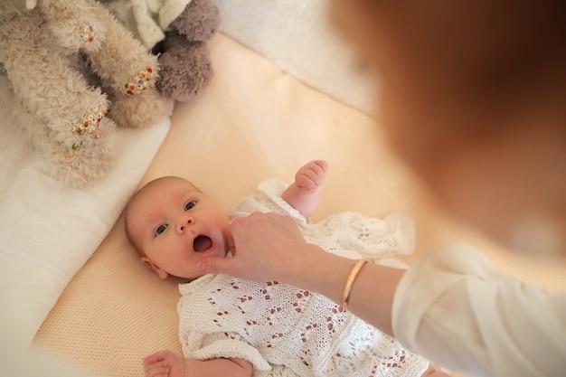 生まれたばかりのかわいい赤ちゃんはベビーベッドに横たわって、母親を見ています