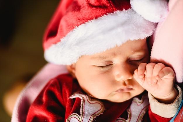 Newborn girl asleep with a santa claus hat