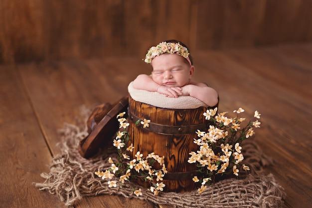 Newborn girl, baby sleeps in a bucket of flowers.