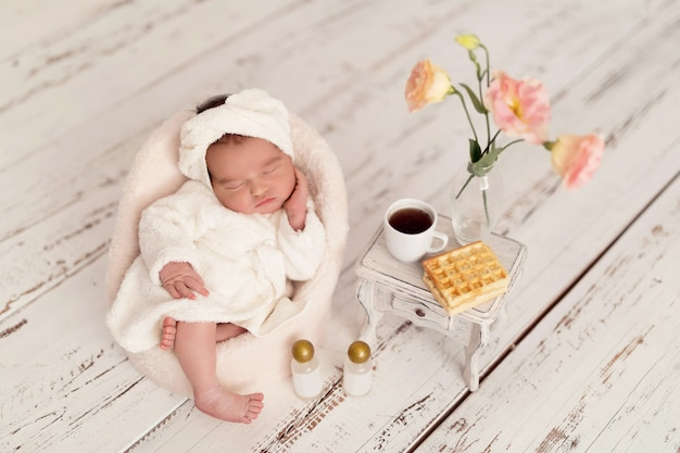 Newborn girl lying in a chair in a bathrobe after spa treatments.