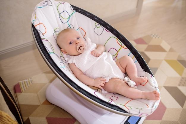 電気ブランコに座っている新生児の女の子