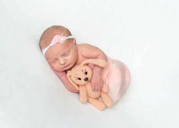 Новорожденная девочка спит и обнимает игрушку