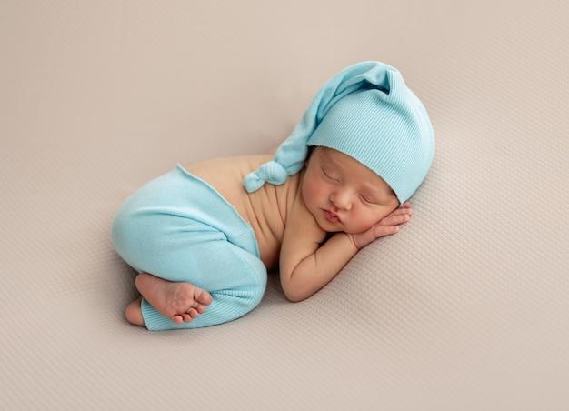 Новорожденный в синей шляпе и штанах спит лежа на животе