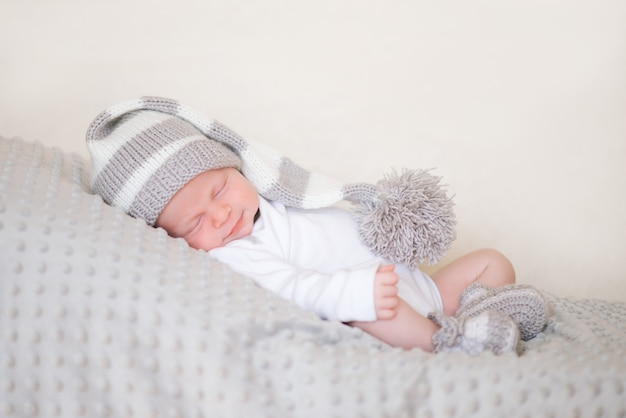 Newborn infant, the baby is sleeping lying on his stomach on a soft blanket