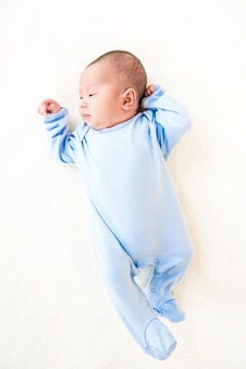 Newborn lovely cute baby lying on white sheet