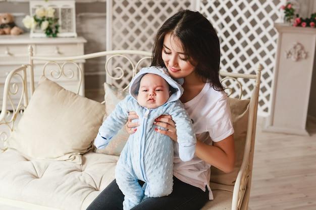 生まれたばかりの混血の男の子と彼の若い母親。アジアとイギリスの生まれたばかりの赤ちゃん。