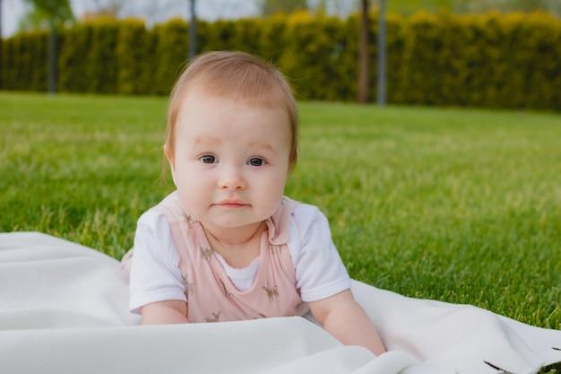공원에서 잔디에 흰색 격자 무늬에 누워 신생아 간호 아기 소녀