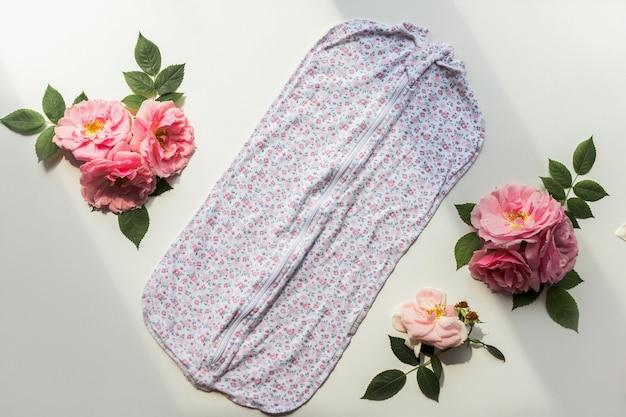 花柄と白い背景で隔離のバラの組成を持つ新生児ロンパース