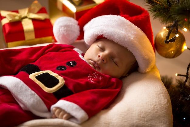 Новорожденный санта-младенец спит с рождественскими подарками в гостиной