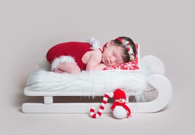 Newborn in santa's bodysuit sleeping