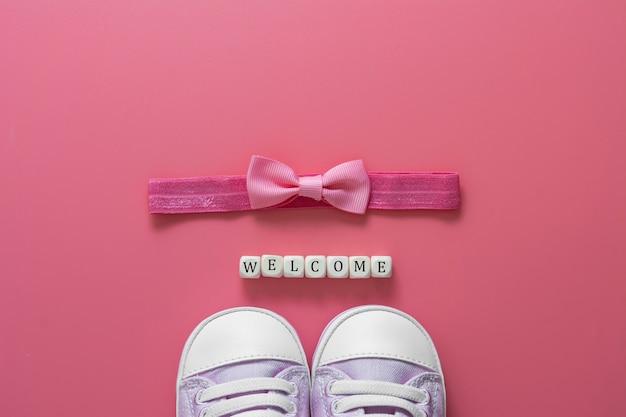新生児靴、お辞儀、ウェルカムワード。赤ちゃんフラット横たわっていた。ベビーシャワーのコンセプト