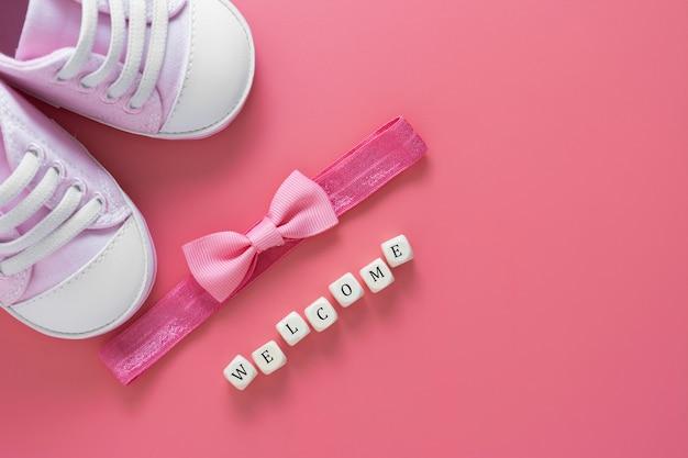 新生児靴、お辞儀、ウェルカムワード。赤ちゃんフラット横たわっていた。