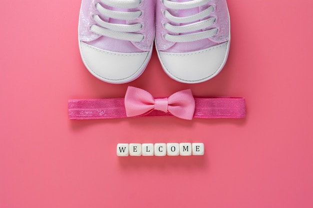 Newborn shoes, bow and welcome words. baby flat lay.