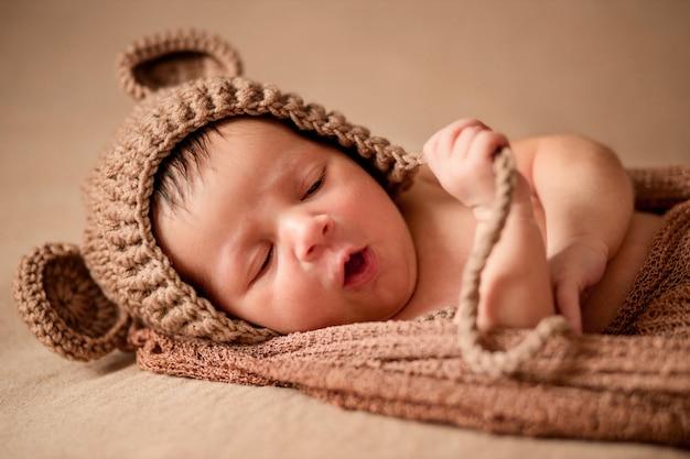 니트 모자에 신생아 잠자는 아기는 갈색 천으로 놓여 있습니다.